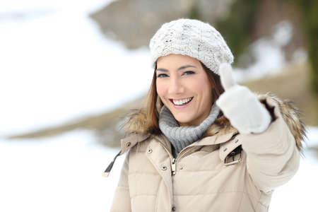 Happy woman with thumb up keeping warm in winter in a snowy mountain