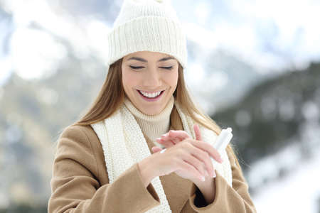 Front view portrait of a happy woman applying moisturizer cream to hydrate hands with a snowy mountain in the background Stockfoto