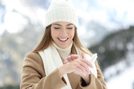 Vooraanzichtportret van een gelukkige vrouw die vochtinbrengende crèmeroom toepast om handen met een sneeuwberg op de achtergrond te hydrateren Stockfoto