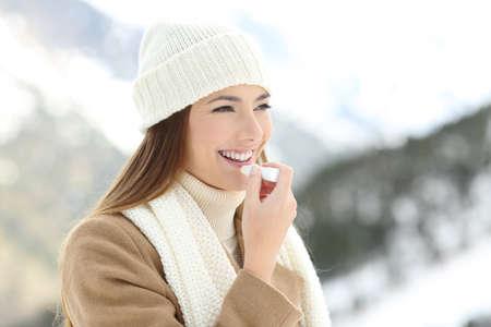 Portrét šťastná žena použití balzám na rty v zimě s zasněžené hory v pozadí