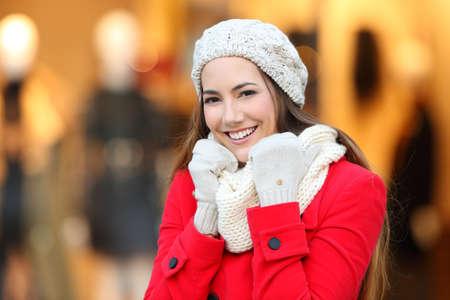 Portrait of a happy woman keeping warm in winter in a mall in winter