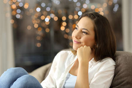 Candid woman dreaming sitting on a couch in the living room at home with little lights in the background