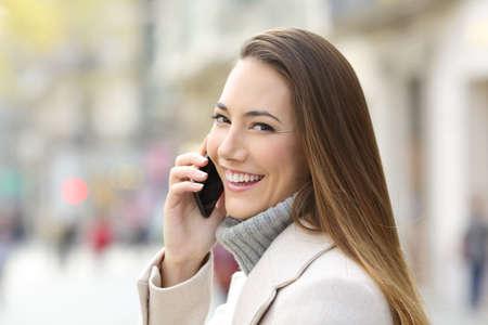 Portrét šťastné dívky telefonuje v zimě a dívá se na vás na ulici