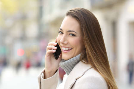 Portrait of a happy girl calling on phone in winter and looking you on the street