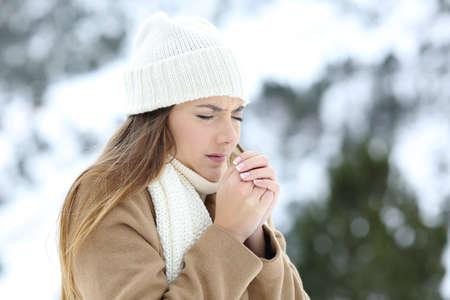 Žena trpící chladem venku v zasněžené hory v zimě