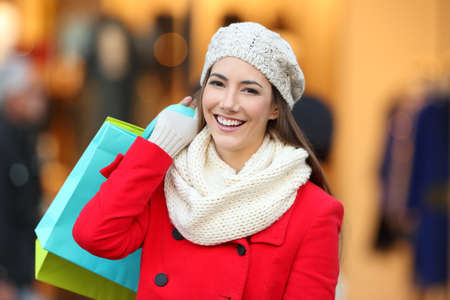 Front view portrait of a happy shopper wearing red coat holding shopping bags looking at you in a mall in winter