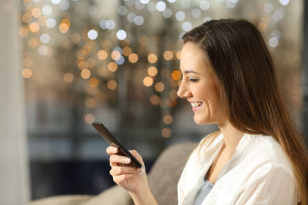 Side view portrait of a happy woman using a smart phone sitting on a sofa at home in the evening with little lights in the background