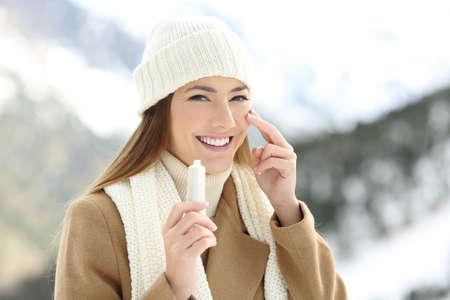 Het portret van een gelukkige vrouw die bevochtigt room in gezicht met een sneeuwberg op de achtergrond van toepassing zijn
