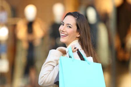Portrét šťastný shopper drží prázdné nákupní tašky na tebe v obchodě v zimě Reklamní fotografie