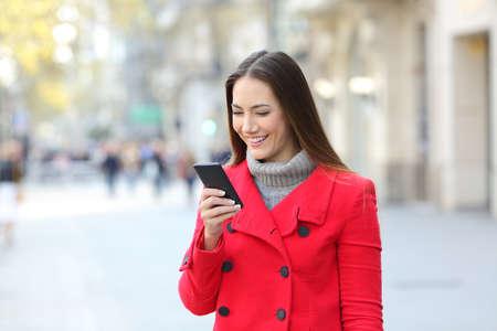 Portrét šťastné dáma nosit červený kabát pomocí chytrý telefon na ulici v zimě Reklamní fotografie