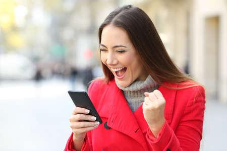 Portret van een opgewekte vrouw die een rode laag dragen die buiten op straat in de winter online winnen