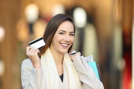 Šťastný zákazník nosí bílý kabát nakupovat a předvádí kreditní kartu v interiéru obchodního domu