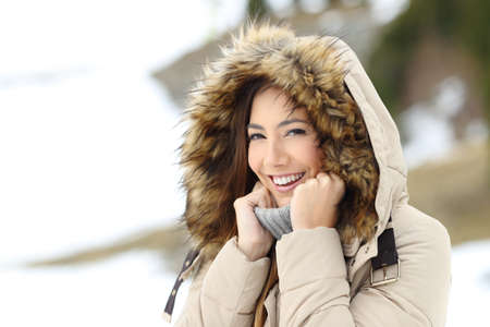 Happy woman keeping warm in a snowy winter on the mountain