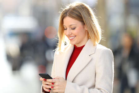 Portrait of a happy blonde lady wearing a white coat writing in a smart phone on the street in winter