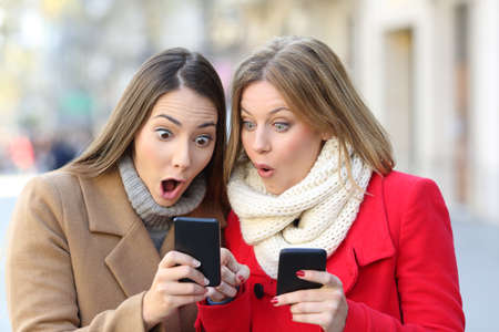 Front view portrait of two amazed women finding on line content on their smart phones on the street in winter