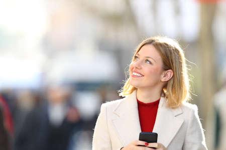 Portrét šťastná žena drží chytrý telefon myšlení a díval se na stranu na ulici v zimě