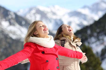 Dva šťastní přátelé dýchají čerstvý vzduch v zimě v zasněžené hory