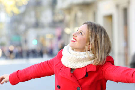 Portrait of a candid woman wearing a red coat joking on the street and looking at side   in winter Reklamní fotografie