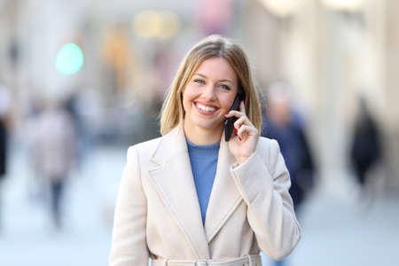 Čelní pohled portrét šťastná dáma volání na telefon a díval se na kameru na ulici v zimě Reklamní fotografie