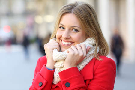Portrait of a beauty woman wearing a red coat and scarf keeping warm on the street in winter