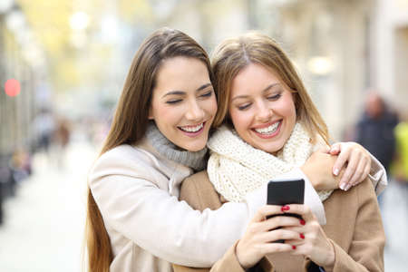 Front view portrait of two cheerful friends watching smart phone content in winter on the street