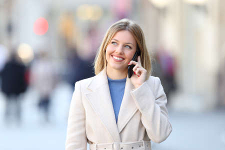 Front view portrait of a woman wearing a white coat calling on phone and looking at side on the street in winter