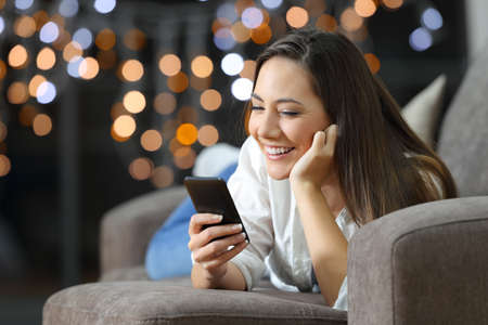 Portrait of a happy girl using a smart phone lying on a sofa in the living room at home in the night with blurred lights in the background
