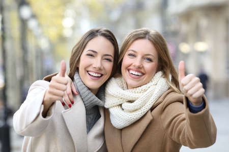 Front view portrait of two friends wearing coats smiling at camera with thumbs up in winter on the street Stock Photo