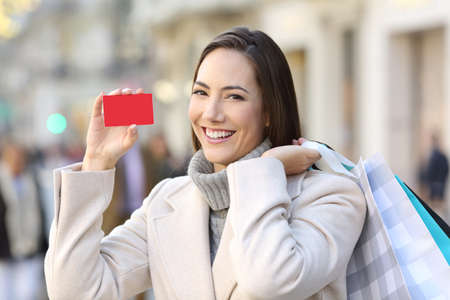 Portrait of a happy customer showing a blank credit card on the street in winter