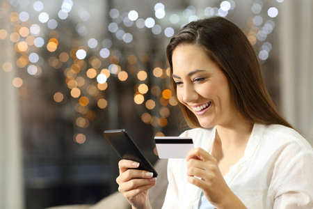 Happy girl buying on line with a credit card and smart phone sitting on a sofa in the living room at home in the night with lights in the background