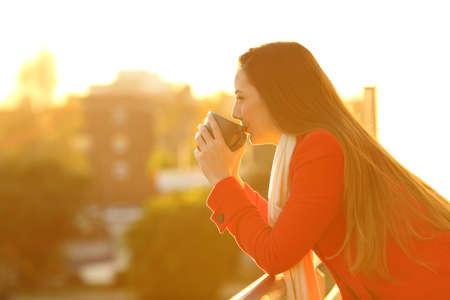 Side view portrait of a pensive woman wearing a red coat drinking coffee outside in a house balcony in winter Banco de Imagens