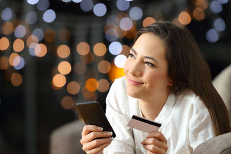 Portrait of a happy woman wondering what to buy on line looking at side lying on a sofa in the living room at home in the night Reklamní fotografie