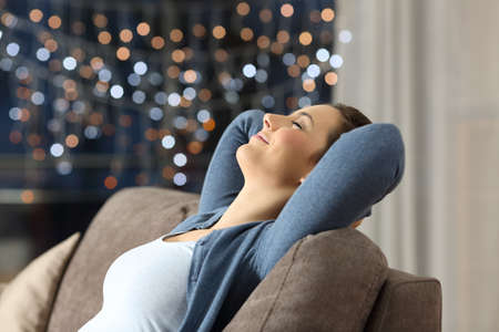 Side view portrait of a relaxed happy woman resting sitting on a couch in the night at home