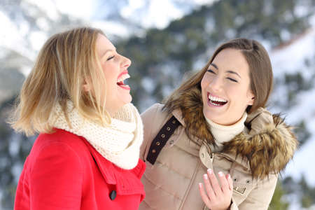 Two happy friends laughing loud enjoying winter holidays in a snowy mountain