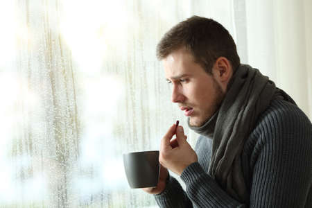Side view portrait of an ill man taking a painkiller pill in a house interior in a rainy day of a cold winter Stock Photo