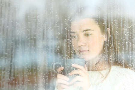 Portrait of a longing teen looking through a window alone at home in a rainy day