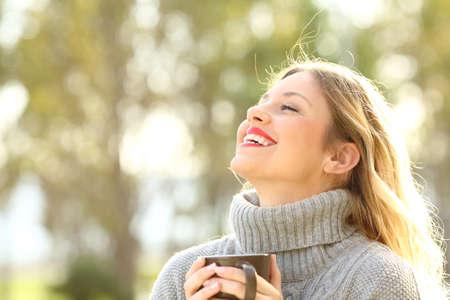 Portret szczęśliwej damy w szarej koszulce oddychającej świeżym powietrzem, trzymając filiżankę kawy w parku w zimie
