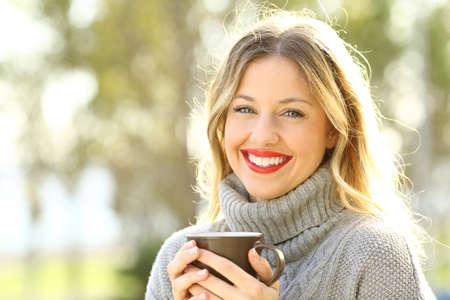 Szczęśliwa kobieta jest ubranym popielatego bydło patrzeje kamerę trzyma filiżankę kawy