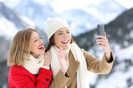 Two happy tourists having a video call with a smart phone in winter holidays in a snowy mountain Stock Photo