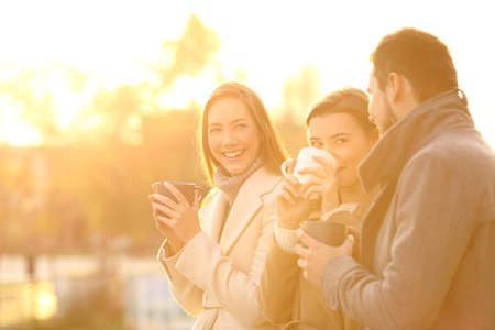 Three funny friends talking outdoors and drinking coffee at sunset Stock Photo