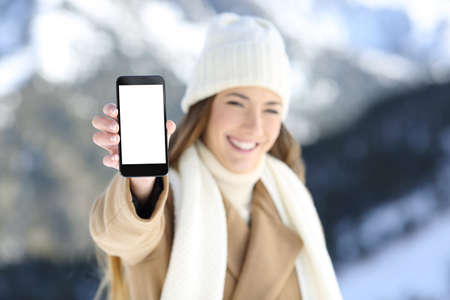 Fronf view portrait of a woman hand showing a smart phone blank screen in winter holidays in a snowy mountain
