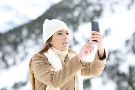 눈 덮인 산에서 겨울 휴가에 휴대 전화 범위를 검색하는 절망적 인 여자
