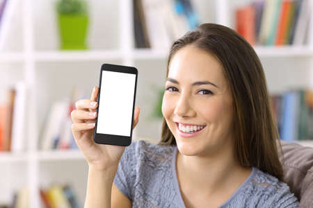 Happy lady showing a blank smart phone screen sitting on a sofa at home
