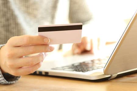 Close-up de uma mão de menina usando um cartão de crédito para pagar on-line com um laptop em um desktop em casa