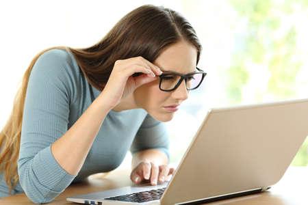 Frau mit den Sehvermögenproblemen, die versuchen, auf Linie Inhalt in einem Laptop zu Hause zu lesen