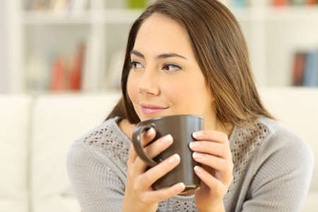 Portrait of a pensive woman holding a coffee mug looking at side sitting on a sofa in the living room at home Stock Photo