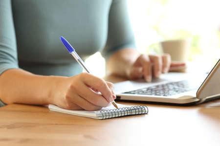 Schließen Sie oben von den Händen einer Dame auf der Linie, die zu Hause Kenntnisse in einem Notizbuch und in einem Laptop auf einem Schreibtisch nimmt Standard-Bild