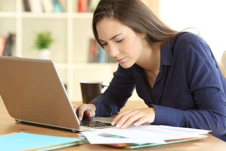 Geconcentreerde ondernemer die documenten online vergelijkt met een laptopzitting op een desktop thuis