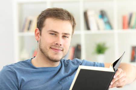 Front view portrait of a man reading a book looking at you sitting on a sofa at home