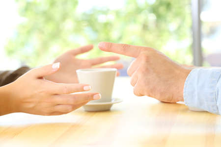 Close up of a friends hands arguing in a restaurant table or home
